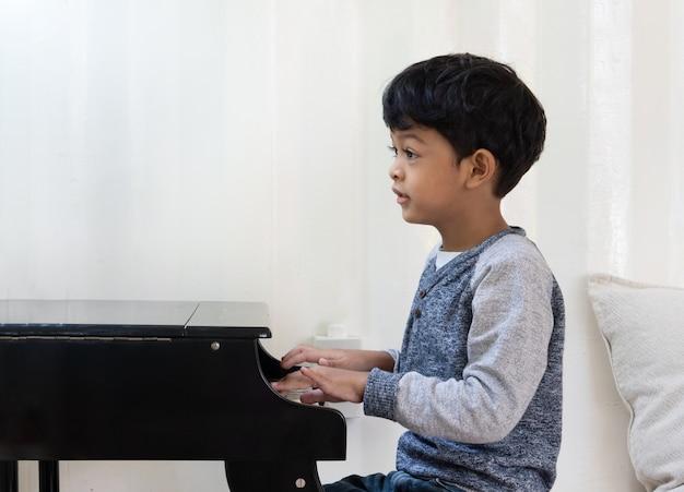 Niño asiático japonés tocando el piano