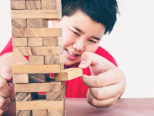 Un niño asiático está jugando al juego de la torre de bloques de madera para practicar habilidades físicas y mentales.