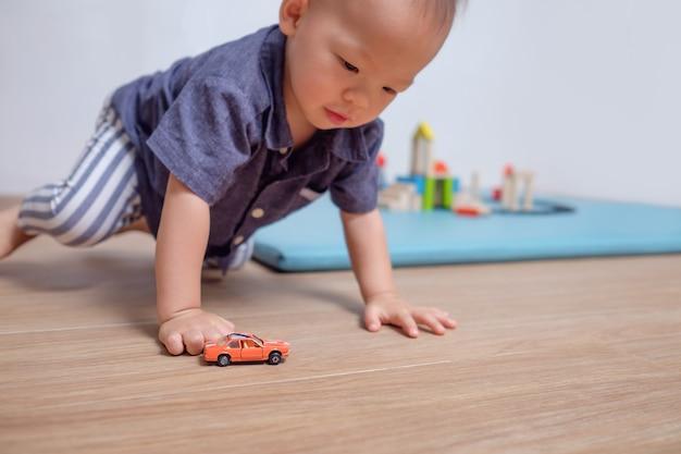Niño asiático jugando con coche de juguete en casa