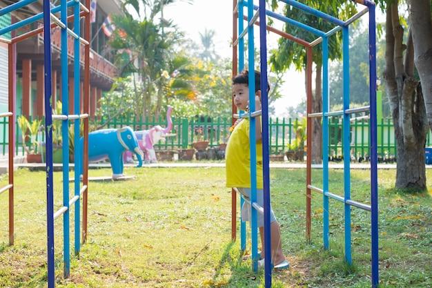 Niño asiático jugando en el patio de recreo