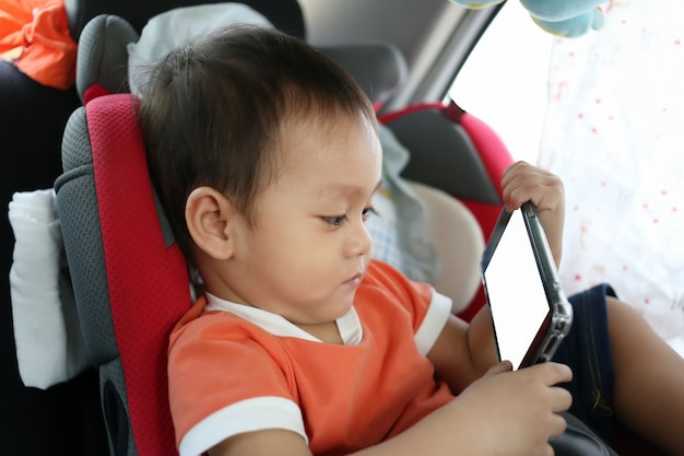 Un niño asiático está jugando un teléfono inteligente.