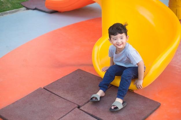 Niño asiático jugando tobogán en el patio de recreo