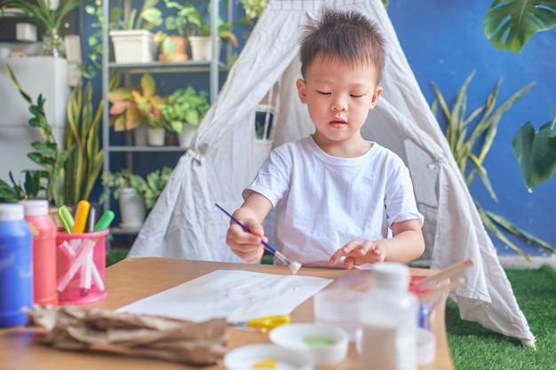 Un niño asiático de kindergarten de 4 años disfruta haciendo manualidades en casa, juguetes de bricolaje para niños del concepto de materiales reciclables