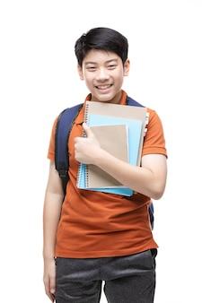 Niño asiático lindo con efectos de escritorio de la escuela en blanco.