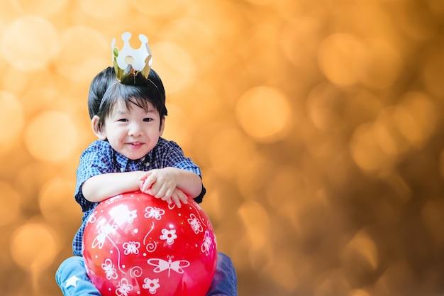 Niño asiático lindo del primer con la corona y el globo de papel en fiesta de cumpleaños en fondo texturizado bokeh ligero marrón borroso con el espacio de la copia