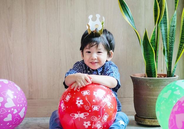 El niño asiático lindo del primer con la corona y el globo de papel en fiesta de cumpleaños en sitio texturizó el fondo con el espacio de la copia
