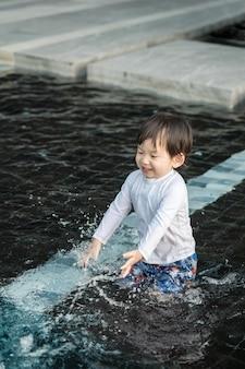El niño asiático lindo del primer goza en la piscina texturizada