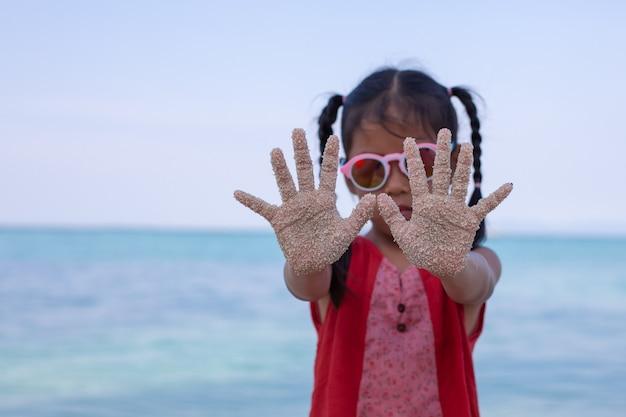Niño asiático manos con arena divirtiéndose en la playa