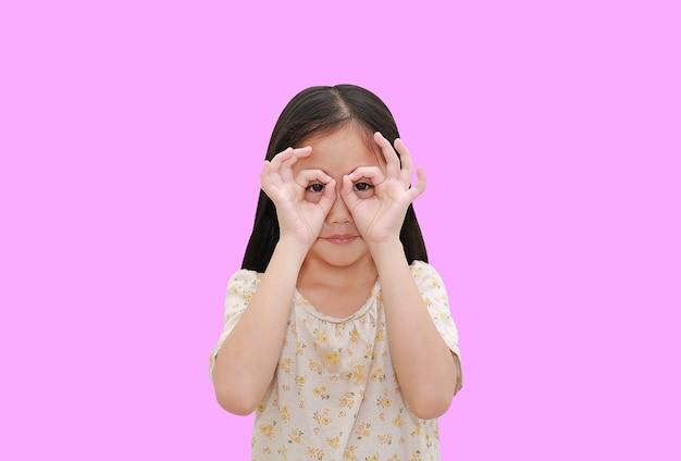 Niño asiático mirando a través de binoculares imaginarios sobre fondo rosa aislado con trazado de recorte.