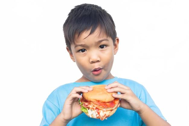 Niño asiático mordiendo y comiendo una hamburguesa.