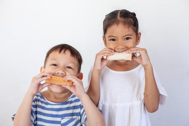 Niño asiático niño y niña comiendo pan juntos antes de ir a la escuela