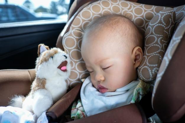 Niño asiático del niño pequeño que duerme en asiento de carro. niño viajando seguridad en la carretera. manera segura de viajar con cinturones de seguridad abrochados en vehículos con concepto de niño pequeño