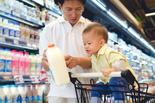 Niño asiático del padre y del muchacho que elige el producto de leche en tienda de comestibles