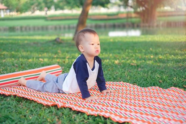 El niño asiático practica yoga en cobra pose y al aire libre.