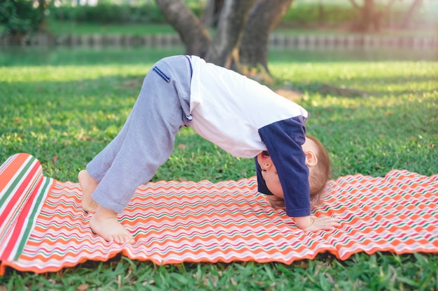 El niño asiático practica yoga en postura de perro boca abajo y medita al aire libre.