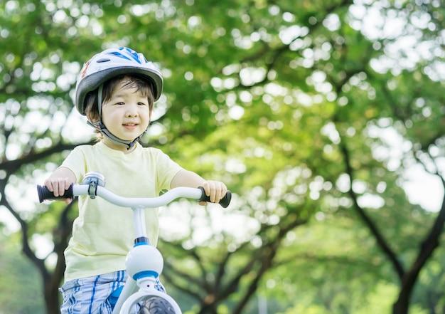 El niño asiático del primer monta una bicicleta en árbol verde en el fondo del parque