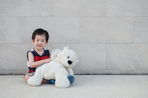 El niño asiático del primer con la muñeca del oso se sienta en el camino en el fondo texturizado pared de piedra de mármol