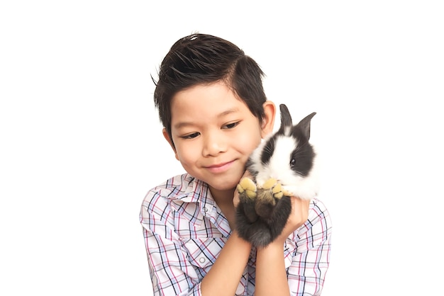 Niño asiático que juega con el conejo encantador del bebé aislado sobre blanco