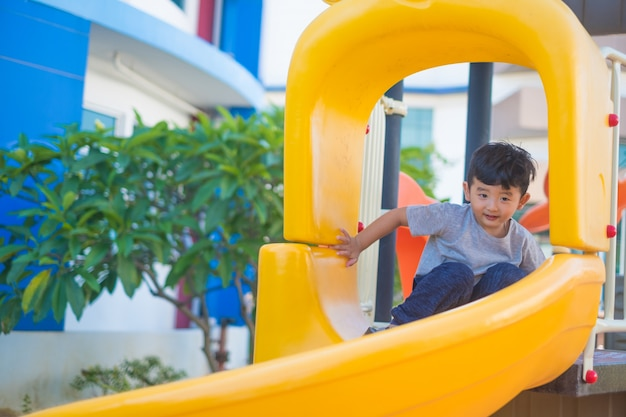 Niño asiático que juega la diapositiva en el patio bajo la luz del sol en verano, niño feliz en guardería o patio de la escuela preescolar.