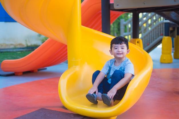 Niño asiático que juega la diapositiva en el patio bajo la luz del sol en verano