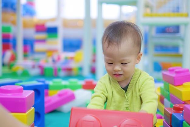 Niño asiático que lleva el suéter verde que se divierte que juega con los bloques plásticos coloridos grandes interiores.