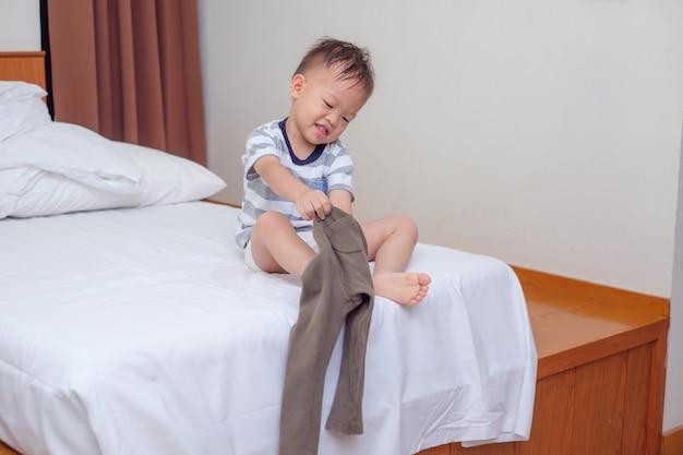 Niño asiático que pone su ropa.