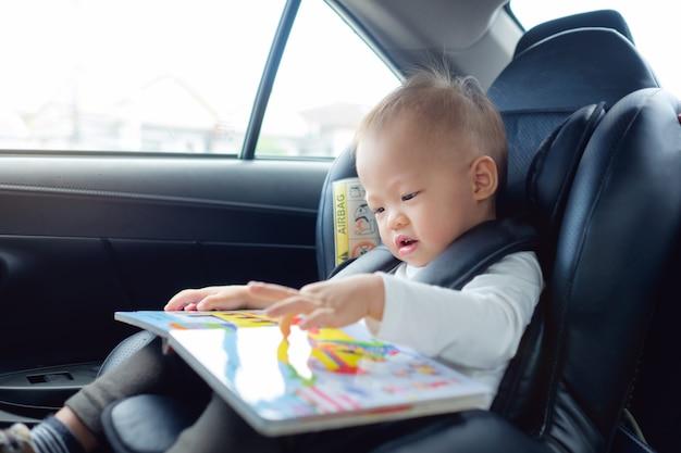 El niño asiático que se sienta en la tenencia del asiento de carro y goza el libro de lectura