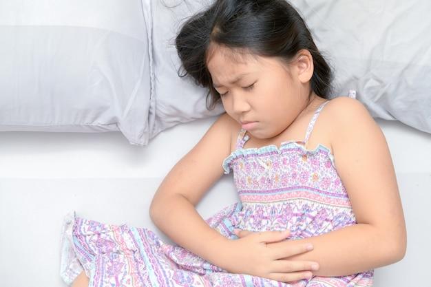 Niño asiático que sufre de dolor de estómago
