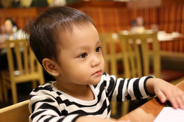 Un niño asiático está sentado atentamente y esperando comida.