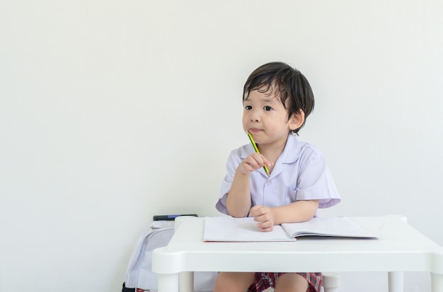Niño asiático sentado para hacer la tarea después de la escuela