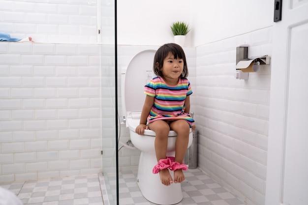 Niño asiático sentado en el inodoro con pantalones abajo