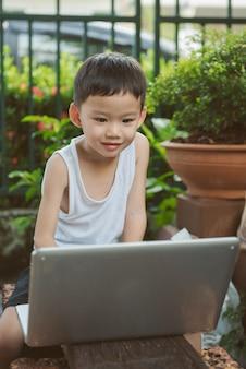 Niño asiático sentado en el jardín y utiliza la computadora portátil para la educación o el juego.
