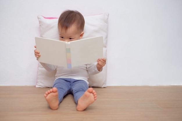Niño asiático sentado en el suelo, apoyado en la almohada