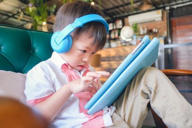 Niño asiático serio del niño pequeño que se sienta en el sillón que juega al juego, mirando un video de la pc digital de la tableta
