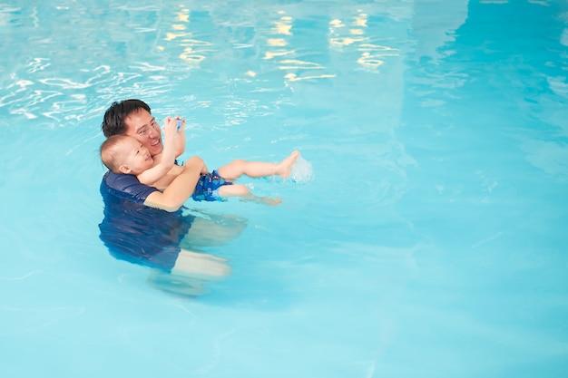El niño asiático sonriente que sostiene el juguete aprende flotar en el agua