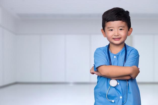 Niño asiático sonriente en el uniforme médico azul que sostiene el estetoscopio