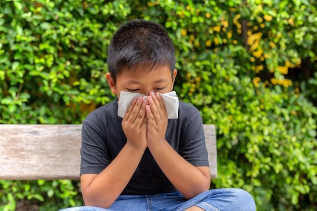 Un niño asiático se sopla la nariz con un pañuelo en el jardín, temporada de gripe, fiebre del heno