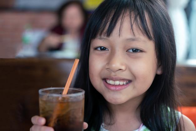 Niño asiático sosteniendo y bebiendo bebidas frías en el restaurante