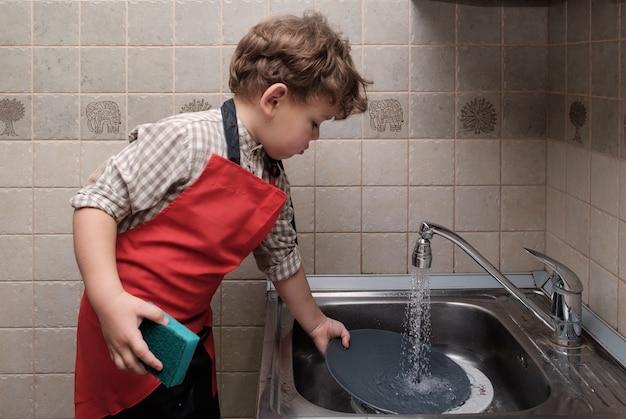 Niño aspecto europeo de la casa lava los platos en el fregadero
