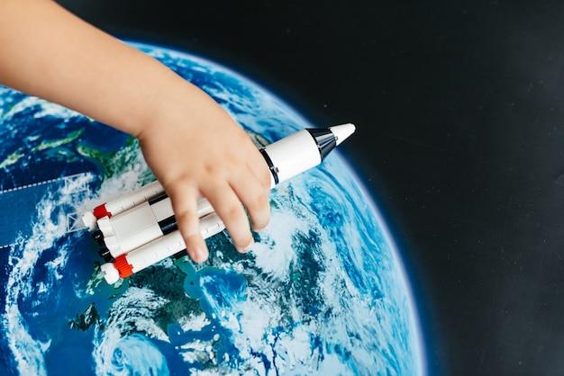 Niño astronauta con cartón cohete de juguete.