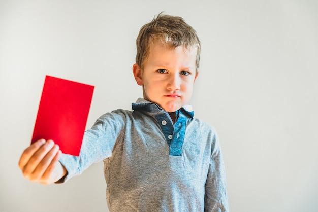 Niño asustado con tarjeta roja anti bullying.