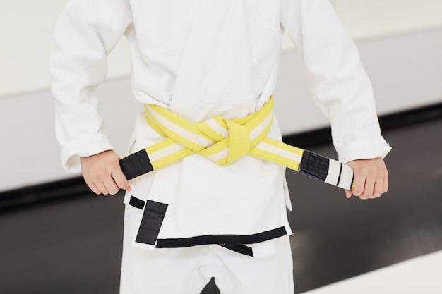 Niño atando el cinturón amarillo