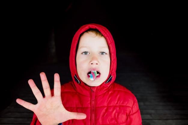 Niño aterrador con capucha roja iluminada con neones es una pose extraña mientras come un caramelo.