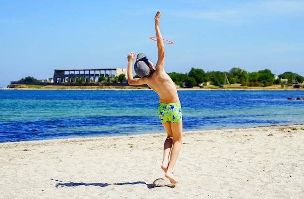 Un niño atrapa un disco de frisbee en la orilla del mar.