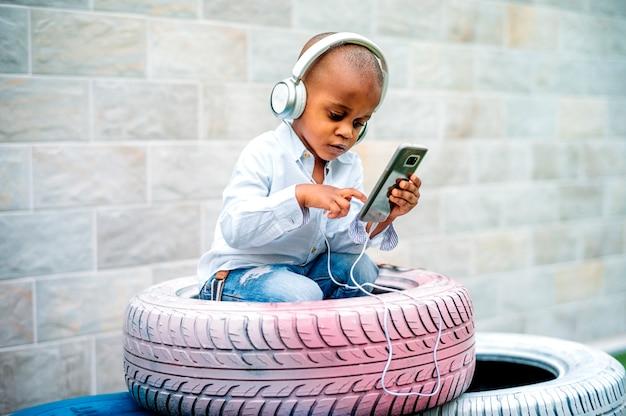 Un niño atrevido escuchando música dentro de un neumático.