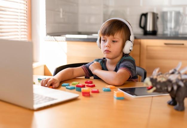 Niño con audífonos asistiendo a cursos en línea