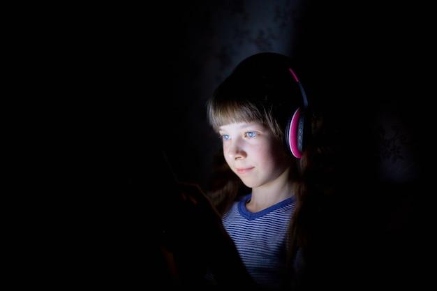 El niño con audífonos inalámbricos escucha música por la noche bajo una manta y mira la tableta.