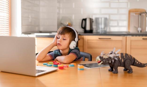Niño con audífonos que asisten a la escuela en línea