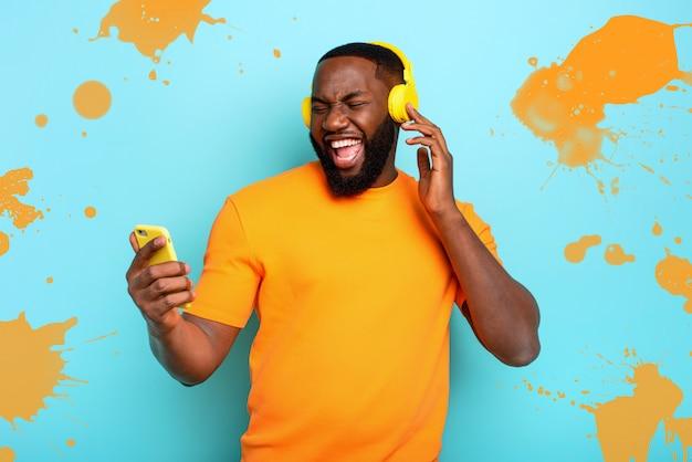 Niño con auriculares amarillos escucha música y bailes. expresión emocional y energética
