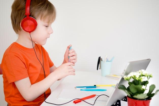 Niño con auriculares y haciendo matemáticas en línea